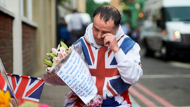A man wrapped in Britain's Union Flag prepares to lay flowers at a police cordon on Borough High Street, near Borough Market, in London on June 5, 2017 in tribute to the victims of the June 3 terror attack on London Bridge and at the market.