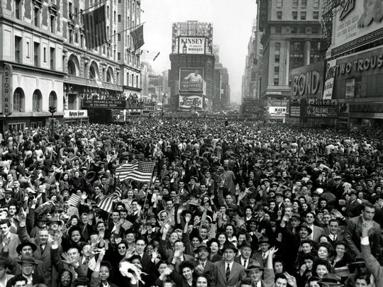 Looking north from 44th St., New York's Times Square is packed with crowds celebrating the news of Germany's unconditional surrender in World War II.