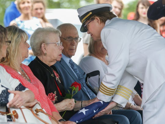 A member of the United States Navy Honor Guard presents the flag that draped Clifford George Goodwin's coffin to Mary Louise Putnam, his niece, at the Diamond Cemetery on Saturday, May 12, 2018. Goodwin was killed at Pearl Harbor during World War II while serving aboard the USS Oklahoma with the U.S. Navy. His remains were recently identified using DNA analysis and he was returned to Missouri from Hawaii to be buried with full military honors.