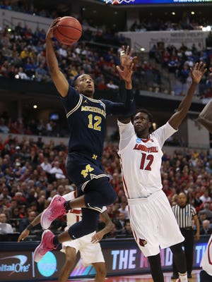 Michigan Wolverines guard Muhammad-Ali Abdur-Rahkman scores against Louisville forward Mangok Mathiang during the second half of U-M's 73-69 win Sunday, March 19 at Bankers Life Fieldhouse in Indianapolis in the second round of the 2017 NCAA tournament.