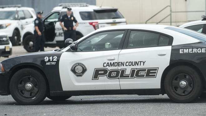 Camden County Poice officers stand in the parking lot of the Camden County Police substation located at 10th and Linden streets in North Camden. 08.11.15
