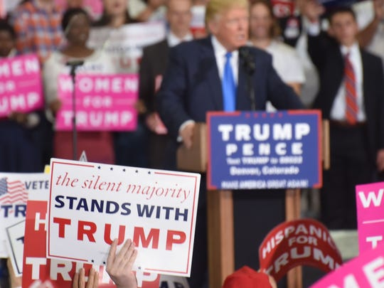 "A supporter at a Trump rally Saturday night in Denver holds a ""silent majority"" sign as the candidate speaks. Many Trump supporters felt the depth of his support wasn't accurately reflected by mainstream media coverage of the race."