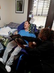 Carlene Beard, an LPN, reads a book with Tristen Shackelford