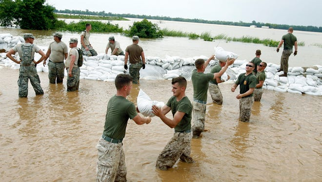 Guardsmen, left, and Marines, right, work together to move sandbags into place. Indiana National Guardsmen and US Marines from Camp Lejeune, NCwork to place sandbags around the tiny town of Elnora, IN as flood waters continue to rise all across southern Indiana on Monday, June 9, 2008.
