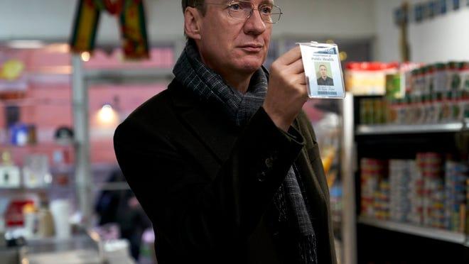 Jim (David Thewlis), a food inspector, flashes his badge at a possible violator.