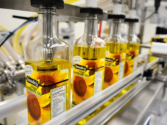 Bottles of Smude's Sunflower Oil are filled May 15, 2014 in Pierz.