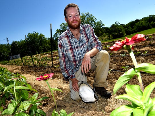 """""""It really comes down to having a passion for being and working outside and working with the plants. ... not necessarily just a passion for the broad-scale side of driving a tractor and cultivating hundreds of acres,"""" said Taylor Yowell of Garden Farmacy, pictured here at his garden in Madison County."""