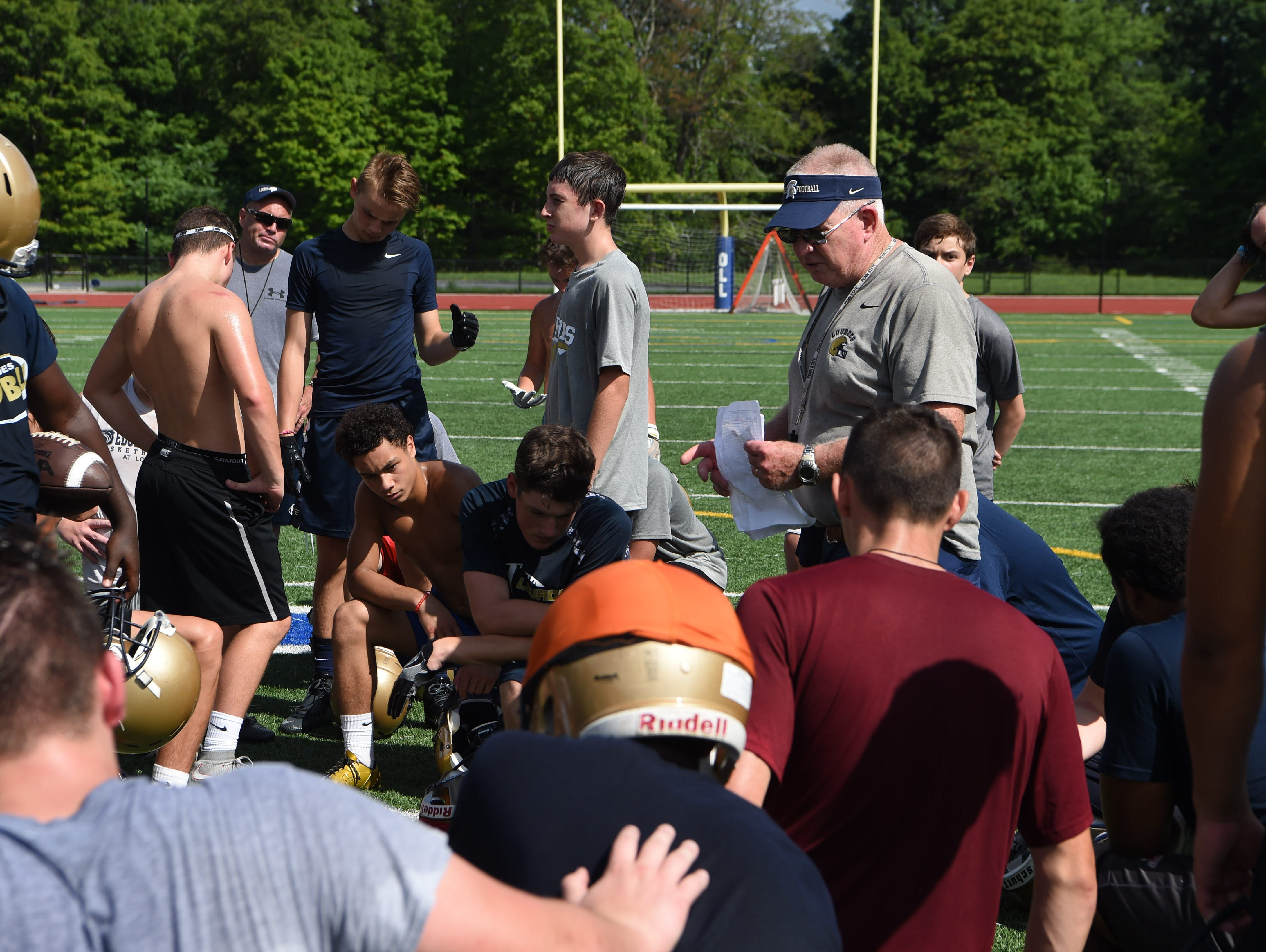 Brian Walsh, center, head coach for Our Lady of Lourdes High School's football team, talks to players before a break in preseason football practice.