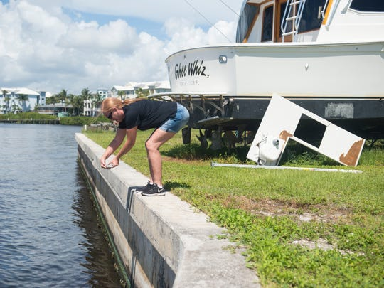 Mary Radabaugh, marine manager at Central Marine, takes a photo of an algae-covered seawall surrounding the property Monday, June 2, 2018, at Central Marine in Stuart. The blue tint of the algae proves to Radabaugh that the algae floating in the St. Lucie River is toxic blue-green algae.