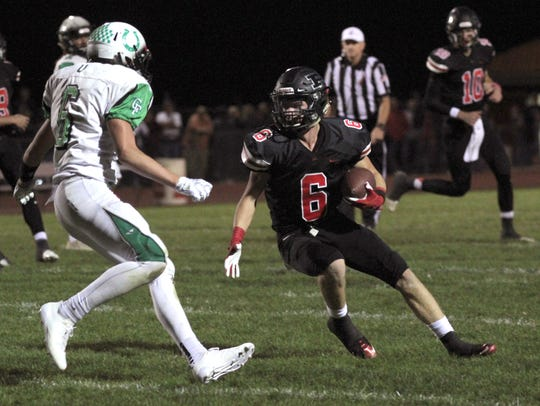 Pleasant's Patrick Blubaugh runs the ball against Clear Fork's Jared Schaefer Friday night. The Colts won 20-17 in overtime to clinch at least a share of the Mid Ohio Athletic Conference football title.