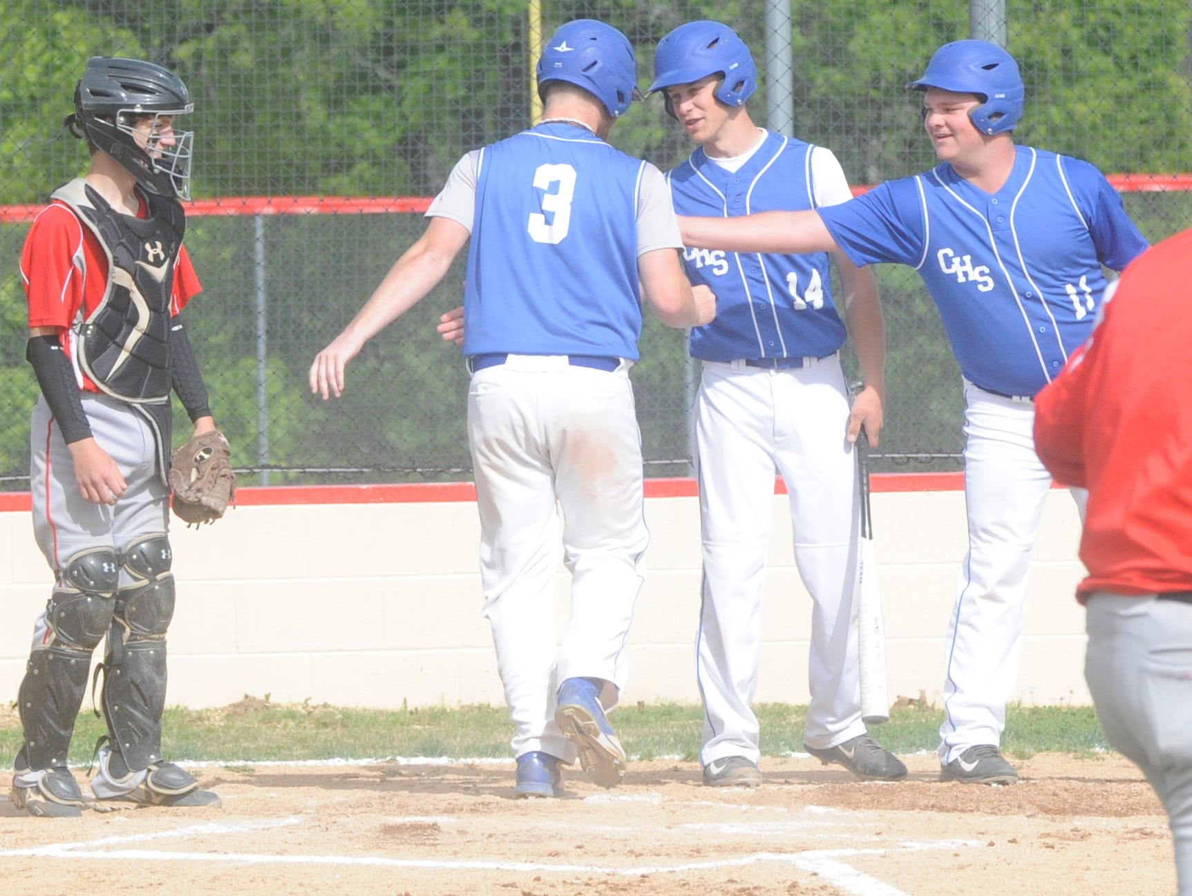 Three of Cotter's six seniors, from left, Ryan Roberts, Brett Walker and Colton Neal, celebrate after scoring a run against Norfork in a game earlier this season.