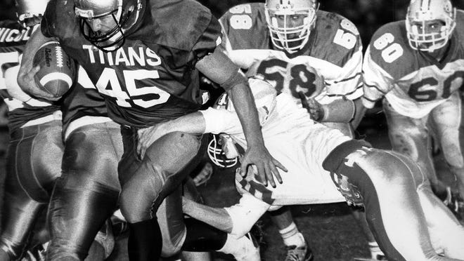 Boylan fullback Tim Scharf (45) runs for yardage against Belvidere in 1992. Scharf was also a three-time all-conference linebacker for the Titans and starred on Northwestern teams that won back-to-back Big Ten titles.