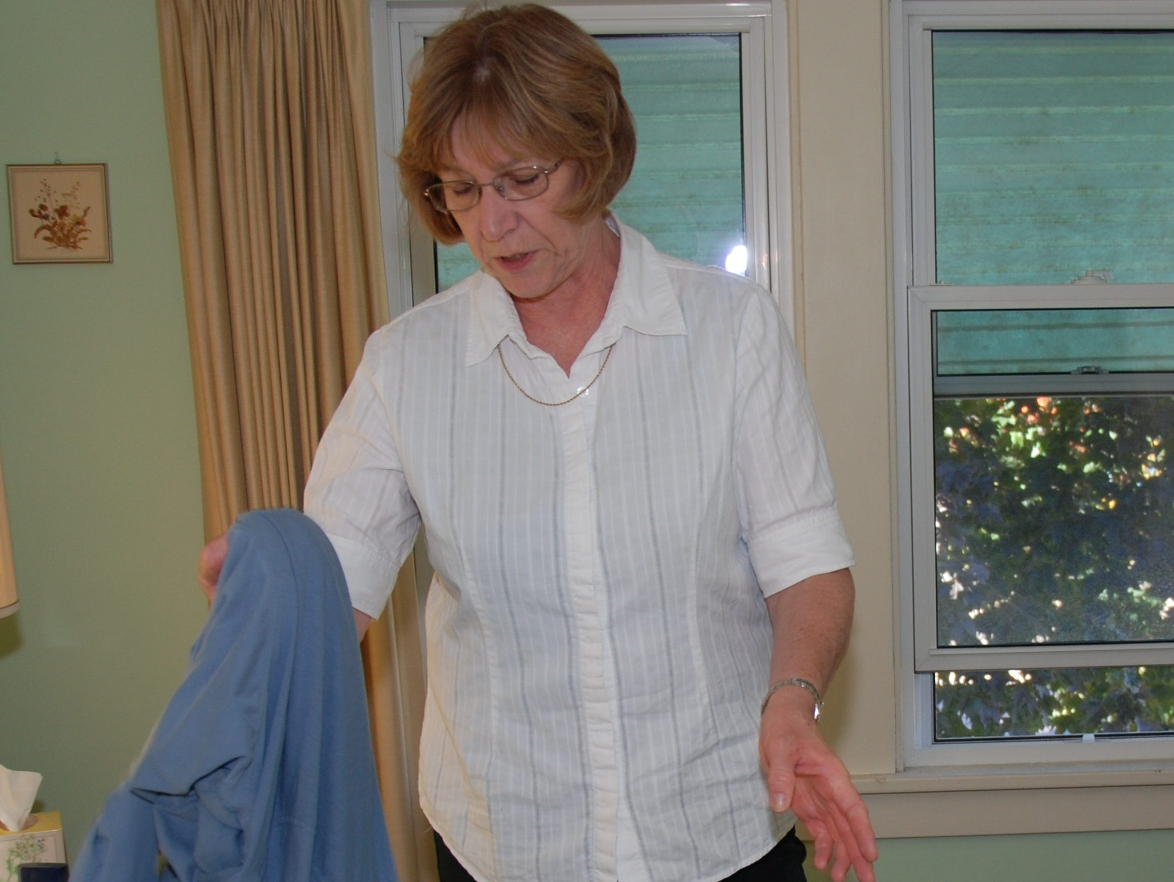 As a personal care aide, Marcia Olson, does laundry,
