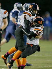 Northville kicker Jake Moody jumps into the arms of