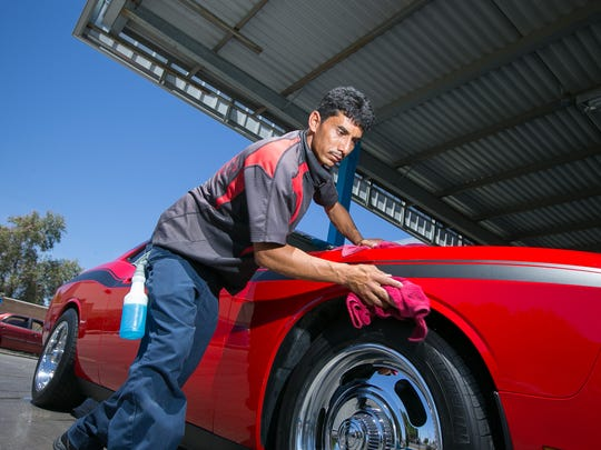 Attendant Hector Oronia dries a car at TNT Car Wash in Surprise on Friday, May 2, 2014.