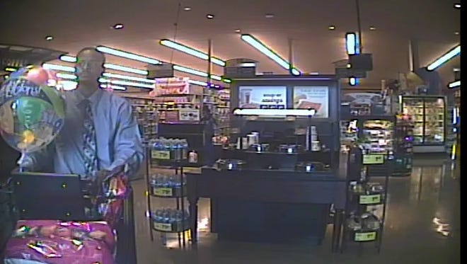 Sparks police released a photo showing a man wearing a tie and carrying balloons walking out of a Safeway grocery store on May 10, 2018. The suspect allegedly grabbed a large amount of high-priced alcohol and walked out without paying.