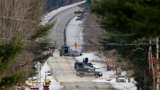 Police officers in tactical gear work on Jan. 1 on Hornbrook Road in Danby as seen from Route 96B as the standoff with David Cady continued.