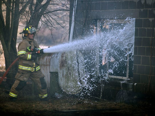 A firefighter shoots water through a busted window,
