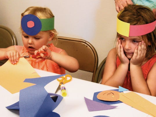 Two-year-old Madison Dickerson, left, and sister Mikaela Dickerson, 5, both of Gilbert, Ariz., make paper hats on Thursday at the Silver City Public Library. The library kicked off its Summer Reading Program on Wednesday, and will have fun activities for youth of all ages throughout the summer. Randal Seyler - Sun-News