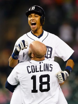 Tigers shortstop Dixon Machado is lifted up by leftfielder Tyler Collins after he hits a walkoff RBI single in the 12th inning of the Tigers' 5-4 win Friday at Comerica Park.