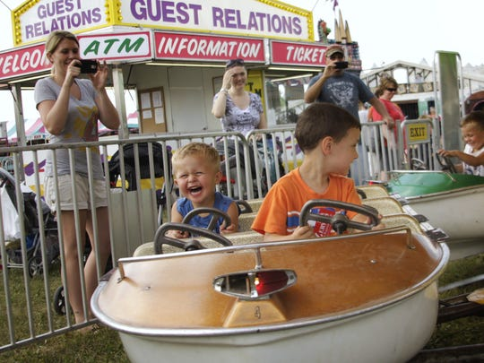 Children laugh and scream as their parents take pictures of them on a ride at the 2016 Sherburne County Fair.
