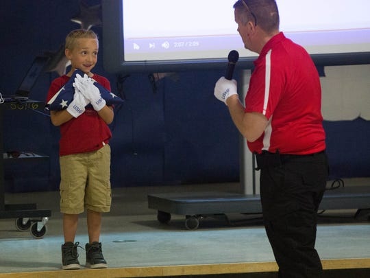 Talen Mays, 7, a second grader at Highland Elementary, holds the Honor Flag as Chris Heisler explains the importance of what he is holding  Friday April 28, 2017 at Highland Elementary.
