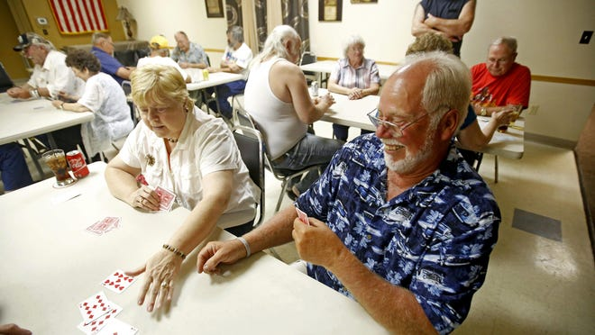 Judy Marcue and Craig Jones enjoy each others company as they compete in a weekly euchre league at the American Legion Post 6 in Dubuque.