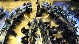 File photograph dated May 6, 2010 shows traders on the floor of the New York Stock Exchange looking at stock trading as the Dow Jones lost almost 1,000 points before recovering to a loss of 505.