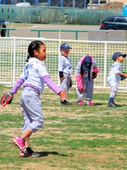 Everyone is practicing some skill at the tee-ball session.