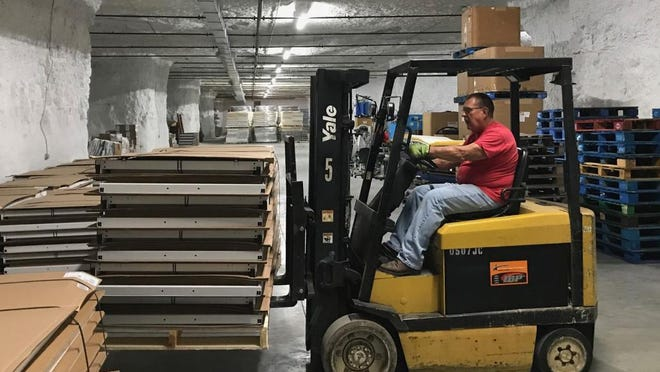 Volunteer worker Gary Hatfield moves supplies in the new Francisan Mission Warehouse space in the caves north of the river.