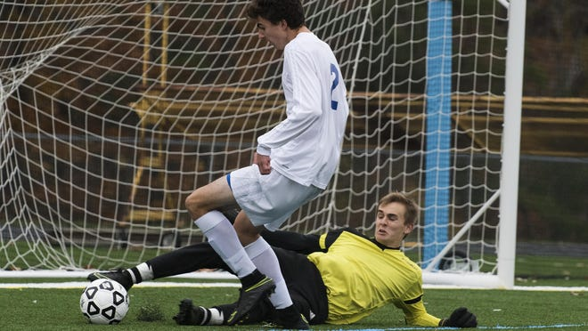 Lake Region's Liam Kennedy makes a foot save on a shot by Milton's Carson Bianchi during the Division II high school boys soccer championship game in November.