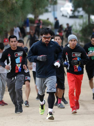 Manny Pacquiao, center, runs along the trail at Griffith