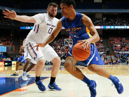 San Jose State's Brandon Clarke moves the ball around Boise State's Nick Duncan (13) during the first half of an NCAA college basketball game in Boise, Idaho, Wednesday, Jan. 20, 2016. (AP Photo/Otto Kitsinger)