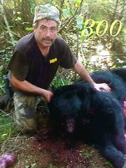 Scott Tadych of Mishicot shows the 300-pound bear he