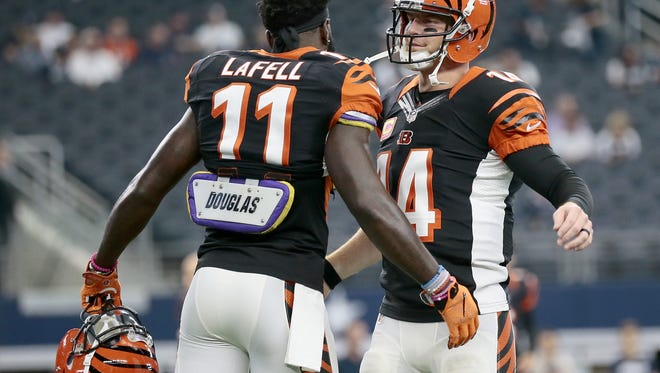 Cincinnati Bengals wide receiver Brandon LaFell (11) and quarterback Andy Dalton (14) hug during warm ups before the NFL Week 5 game between the Dallas Cowboys and the Cincinnati Bengals at AT&T Stadium in Dallas on  Sunday, Oct. 9, 2016.