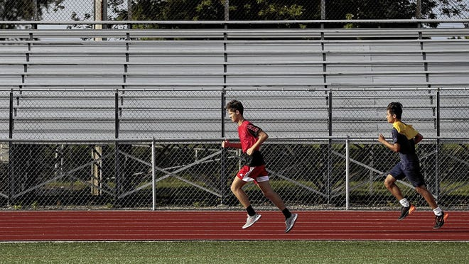 Whitehall junior Jordan Burchnell (left) and sophomore Danny Arriola run laps around the track during soccer practice Aug. 7 at Whitehall. The soccer team was hoping to open the season Friday, Aug. 21, at home against Hilliard Davidson, but was awaiting word from the school district and Gov. Mike DeWine entering the week.