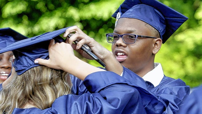 Whetstone High School senior Olivia Mullins gets help with her cap from classmate Tasean Fine during a parent-organized graduation ceremony June 5.