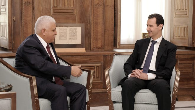 A handout picture released by the official Syrian Arab News Agency (SANA) on May 18, 2017, shows Syrian President Bashar Assad, right, meeting with Iraqi national security adviser Faleh al-Fayad in  Damascus.