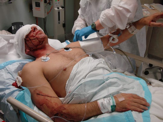 Officer Dane Norem lies in a hospital bed after being stabbed seven times while trying to prevent a suicide in 2012.