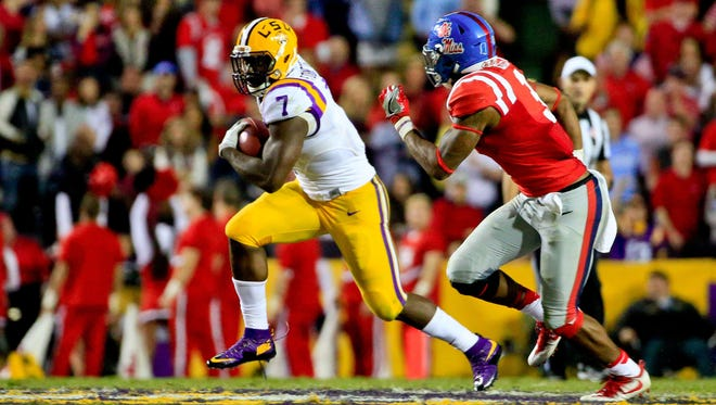 Oct 22, 2016; Baton Rouge, LA, USA; LSU Tigers running back Leonard Fournette (7) runs past Mississippi Rebels linebacker DeMarquis Gates (3) during the second half of a game at Tiger Stadium. LSU defeated Mississippi 38-21. Mandatory Credit: Derick E. Hingle-USA TODAY Sports