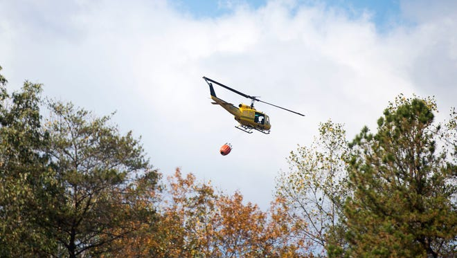 A helicopter carrying 240 gallons of water takes off to assist in the fire containment efforts Wednesday, Nov. 10, 2016 at Lake Lure, N.C.  Unseasonably warm dry weather has deepened a drought that's igniting forest fires across the southeastern U.S.   (Abigail Margulis/The Asheville Citizen-Times via AP)
