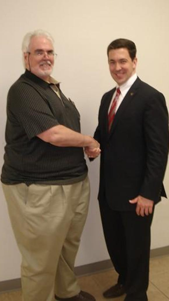 John Mary, also known by his radio name John Bert, is shown in this 2009 photograph shaking hands with state Sen. Chris McDaniel. The two men occasionally co-hosted a radio program together. Mary is facing conspiracy charges in the Rose Cochran video scandal.