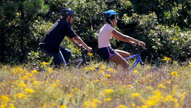 President Obama and his daughter Malia ride bicycles in Manuel F. Correllus State Forest, in West Tisbury, Mass., on the island of Martha's Vineyard, Aug. 23, 2011.