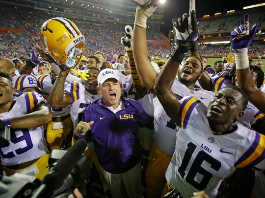 LSU coach Les Miles, center, celebrates with players including safety Rickey Jefferson (29) and defensive back Tre'Davious White (16) after a thrilling win over Florida in 2014.