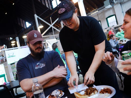 Pepper's Grille co-owner Ginger Hollidge brings food out to Aaron, left, and Veronica Weissner of Shrewsbury.
