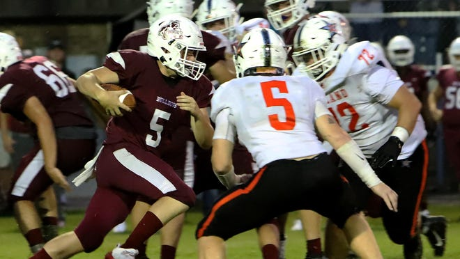 Muldrow's Camden Matthews runs into Roland's defensive line during first quarter play at Muldrow, Thursday, Aug. 27.