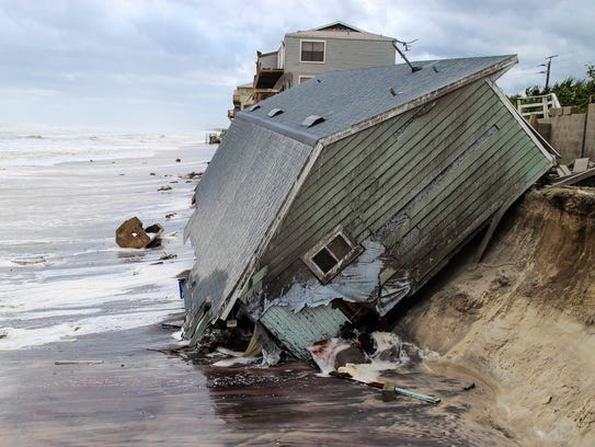A house slides into the Atlantic Ocean on Sept. 11