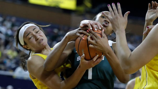 Michigan forward Hailey Brown, left, and Michigan State forward Sidney Cooks (1) fight for the rebound during the first half of an NCAA college basketball game, Tuesday, Jan. 23,2018, in Ann Arbor, Mich.
