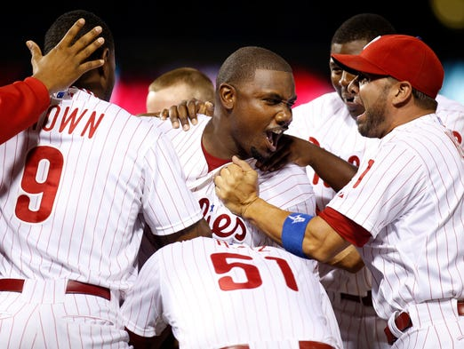 Phillies' Ryan Howard (center) is mobbed by his teammates after getting the game winning RBI in the 15th inning of Philadelphia's 2-1 win against Houston, early Wednesday, August 6, 2014 at Citizens Bank Park in Philadelphia, Pa.