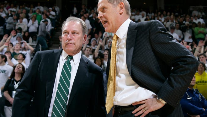 Michigan State coach Tom Izzo, left, and Michigan coach John Beilein talk before an NCAA college basketball game, Sunday, Feb. 1, 2015, in East Lansing, Mich.